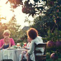 Une famille prenant le petit dejeuner dans le jardin