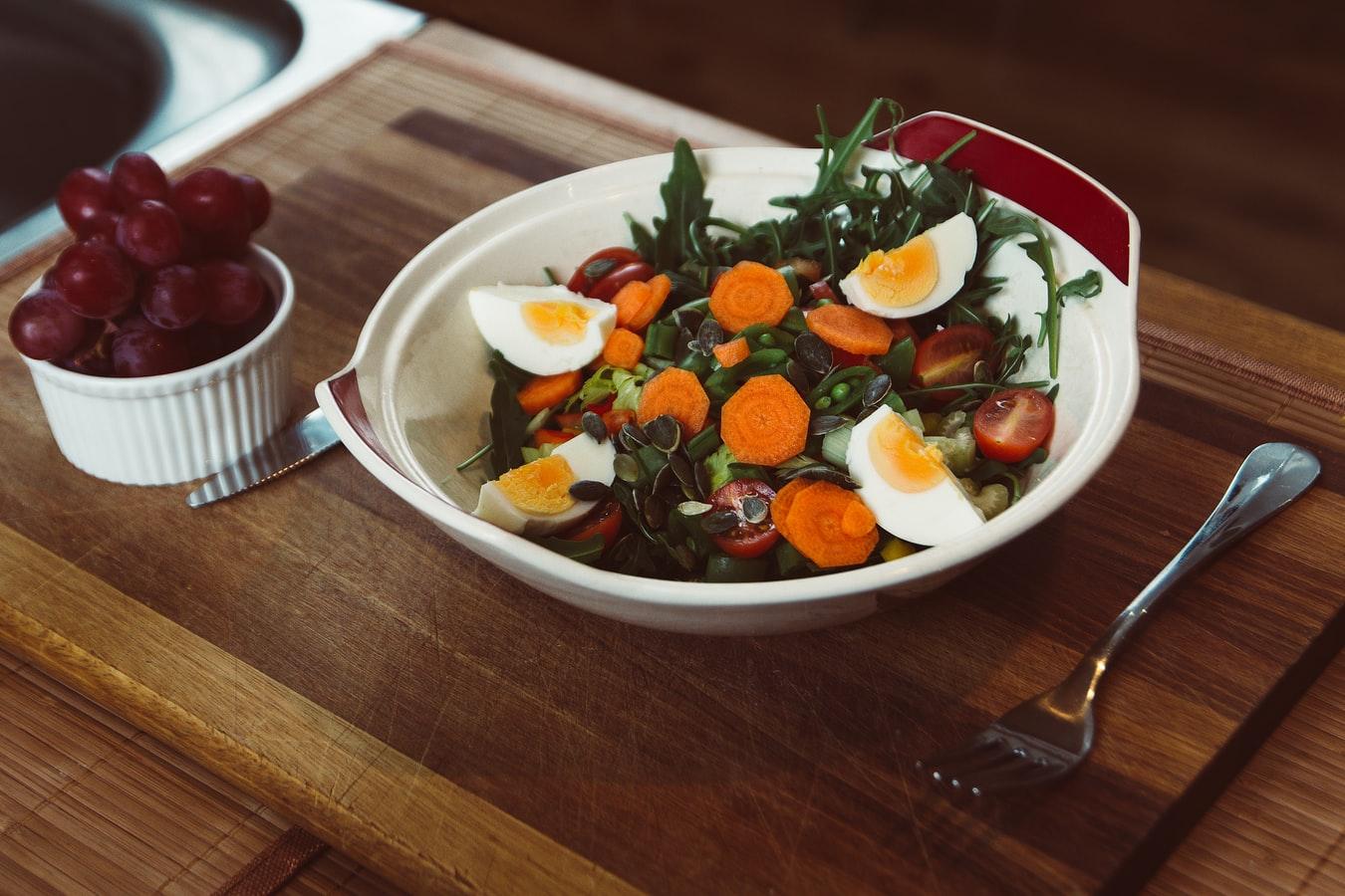 Un plat de salades avec des oeufs et des raisins.