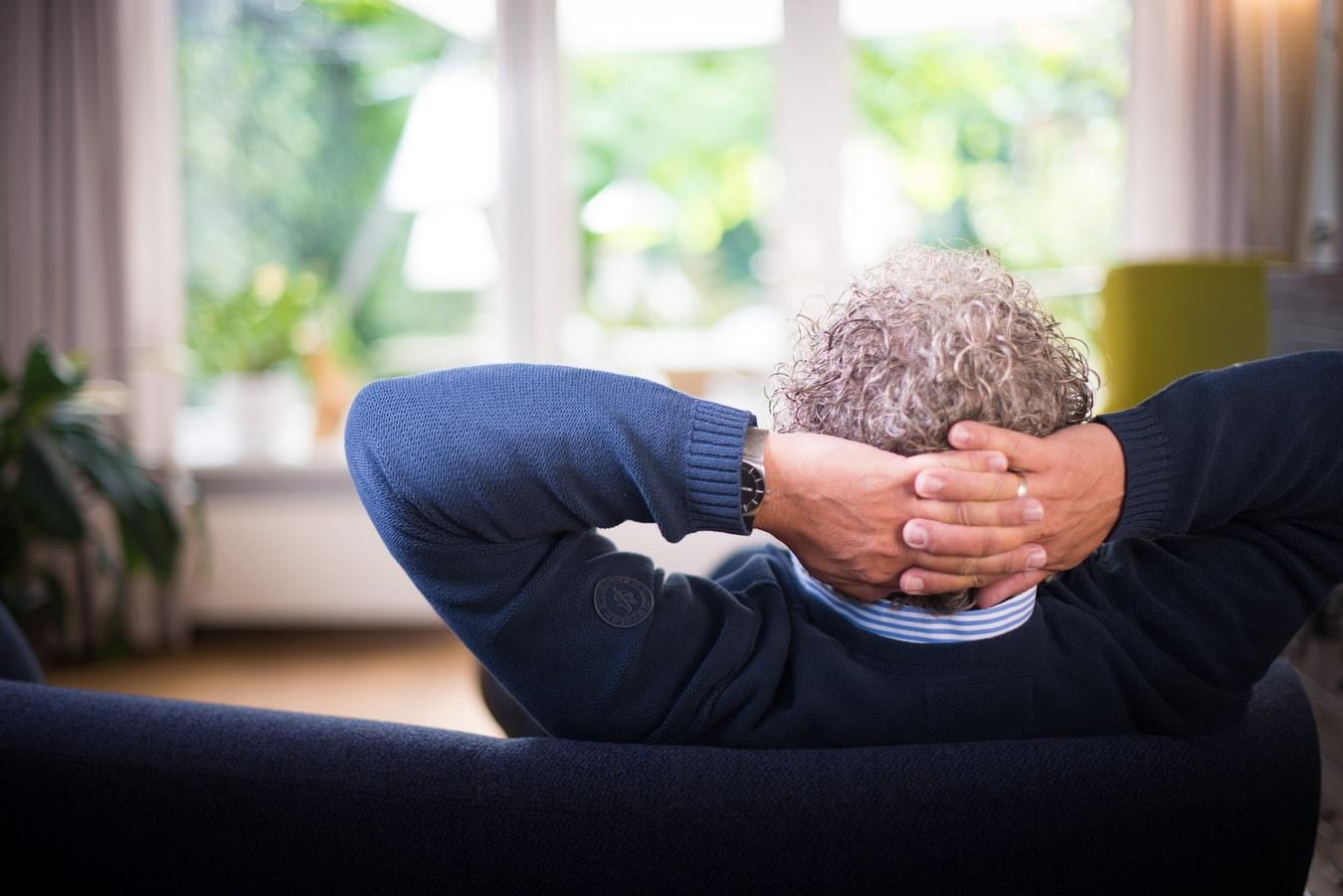 Un homme assis dans son canapé, regardant dans son jardin à travers la fenêtre vitrée (Photo : Unsplash).