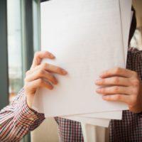 Un homme tenant des papiers.